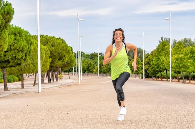 Frontowy widok żeńska atleta ono uśmiecha się podczas gdy ćwiczący bieg w parku. jest brunetką, a jej włosy się poruszają