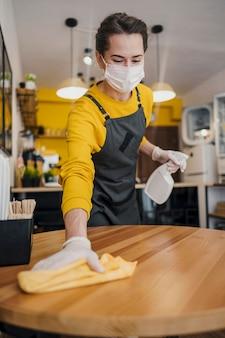 Frontowy widok żeński barista cleaning stół