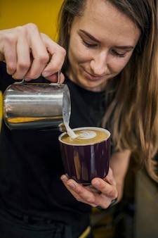 Frontowy widok żeński barista dolewania mleko w kawie