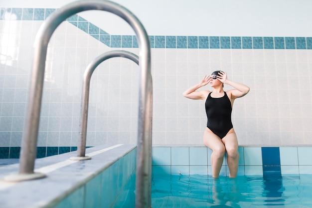 Frontowy widok żeński pływaczki pozować