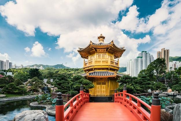 Frontowy widok złota pawilon świątynia z czerwień mostem w nan liana ogródzie, hong kong. azjatycka turystyka, nowoczesne życie w mieście lub biznes finanse i gospodarka