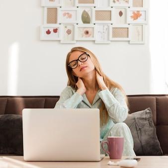 Frontowy widok zmęczona kobieta w piżamach pracuje od domu