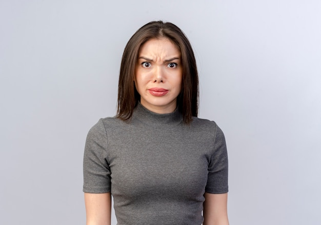 Frowning młoda ładna kobieta patrząc na kamery na białym tle na białym tle z miejsca na kopię