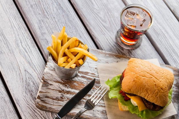 Frytki i burger. sztućce i szkło z colą. apetyczny posiłek w kawiarni. czas na obiad.