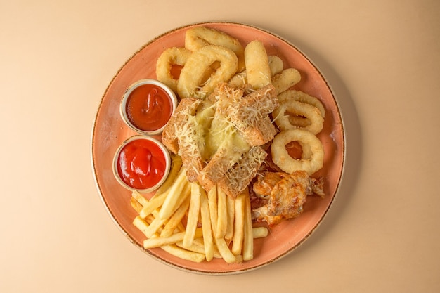 Frytki, krążki cebulowe, skrzydełka z kurczaka, sucharki, przekąska do piwa na dużym talerzu z dwoma sosami na brązowym tle. widok z góry.