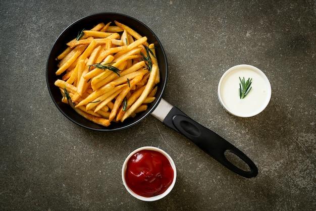Frytki lub chipsy ziemniaczane ze śmietaną i ketchupem