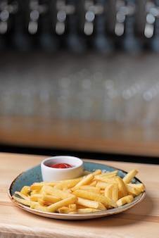 Frytki na talerzu stojącym na drewnianym stole.