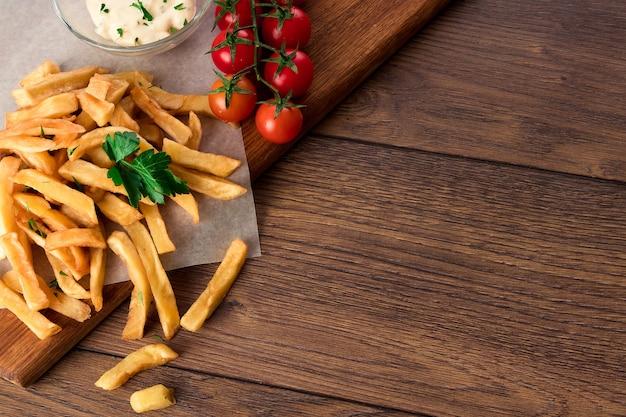 Frytki, pomidory koktajlowe, sos czosnkowy na drewnie