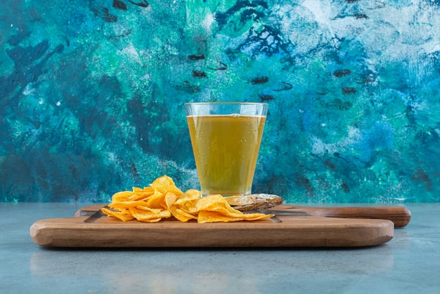 Frytki, ryba i szklanka piwa na desce, na marmurowym stole.