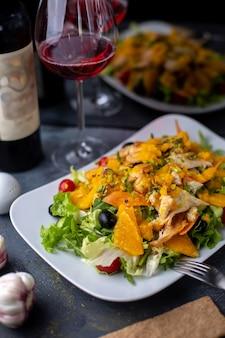 Frytki sałatka pomarańczowa z pokrojonymi warzywami oraz czerwone wino na szarym biurku