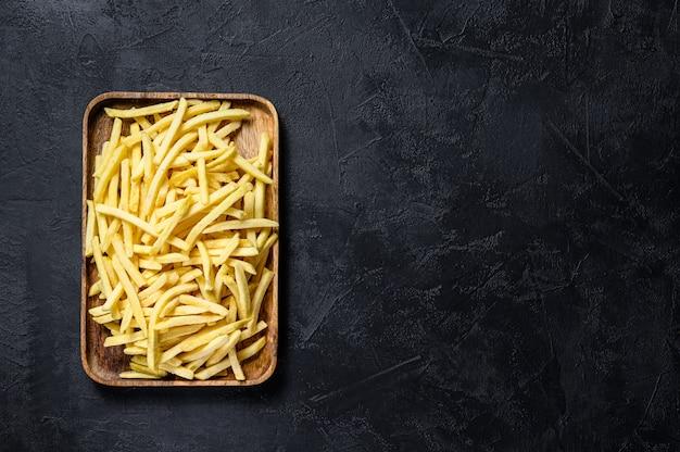Frytki w drewnianej misce. organiczne ziemniaki. czarne tło. widok z góry.