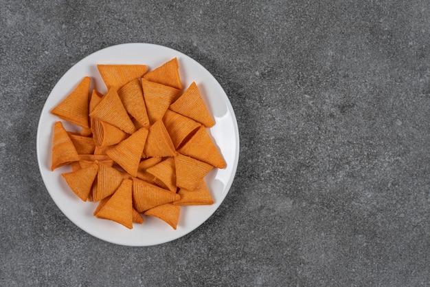 Frytki w kształcie trójkąta na białym talerzu.