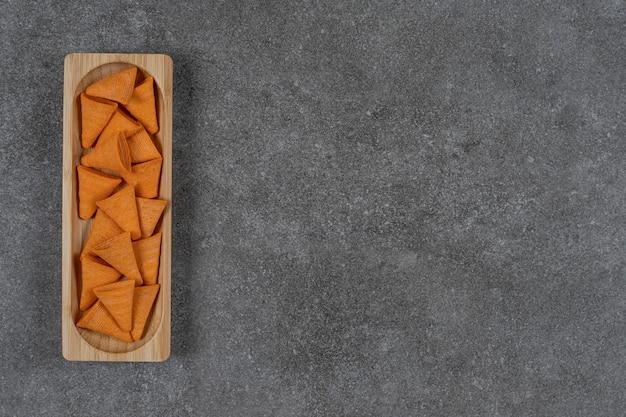 Frytki w kształcie trójkąta na drewnianym talerzu.