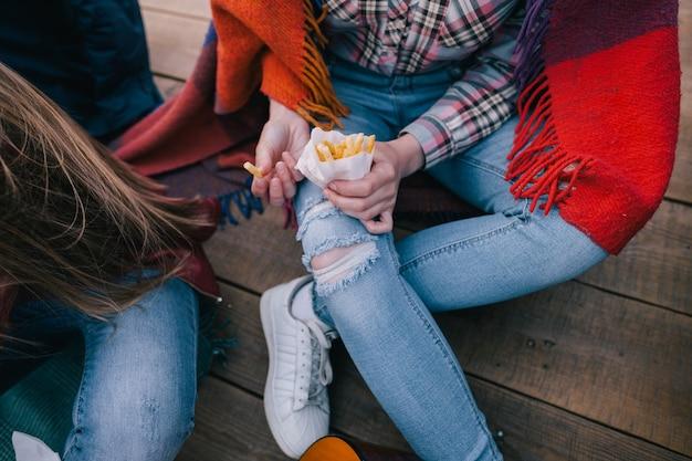 Frytki w rękach stylowej młodej dziewczyny, widok z góry z bliska. nowoczesny styl casual, młodzież i przyjaźń, wspólne spędzanie czasu przy jedzeniu na wynos