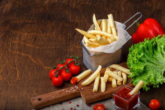 Frytki w siatce z ketchupem, sałatką i pomidorami cherry na drewnianym brązowym stole