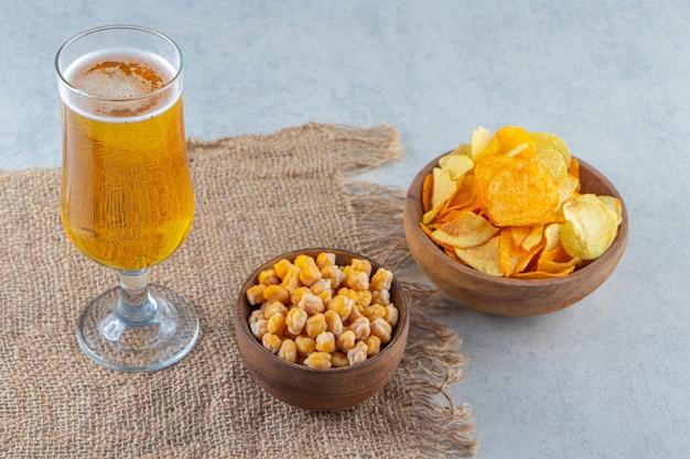 Frytki z ciecierzycy i szklanki do piwa na serwetce z juty, na marmurowej powierzchni.