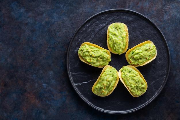 Frytki z guacamole na czarnym talerzu. meksykański sos guacamole z frytkami na ciemnym tle. koncepcja meksykańskie jedzenie w kształcie kwiatu. skopiuj miejsce. widok z góry