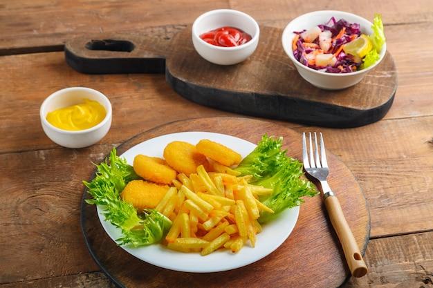 Frytki z nuggetsami z kurczaka obok sosu serowego i ketchupu w łódce z sosem i surówką na drewnianych deskach. zdjęcie poziome