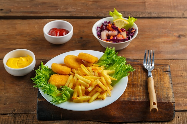 Frytki z nuggetsami z kurczaka obok sosu serowego i ketchupu w sosie łódce i sałatka na drewnianym stole obok widelca. zdjęcie poziome