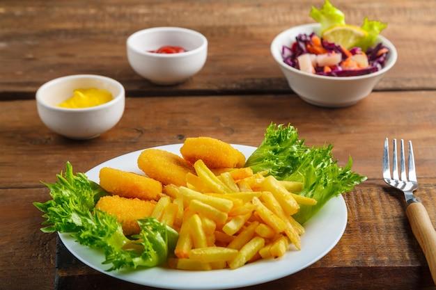 Frytki z nuggetsami z kurczaka obok sosu serowego i ketchupu w sosie łódce oraz sałatka na drewnianych deskach obok widelca. zdjęcie poziome
