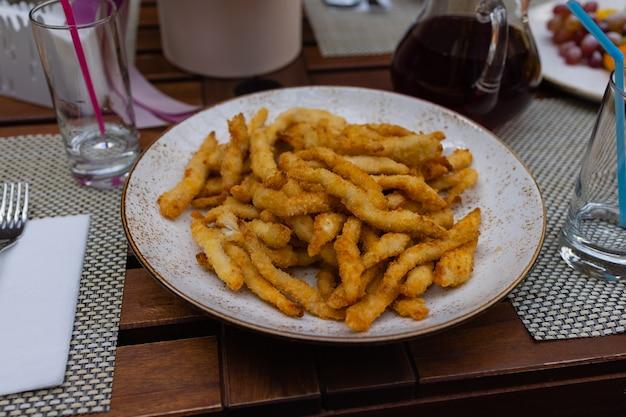 Frytki z serem w proszku i sosem majonezowym służą na czarnym talerzu na tle żywności lub tekstury.