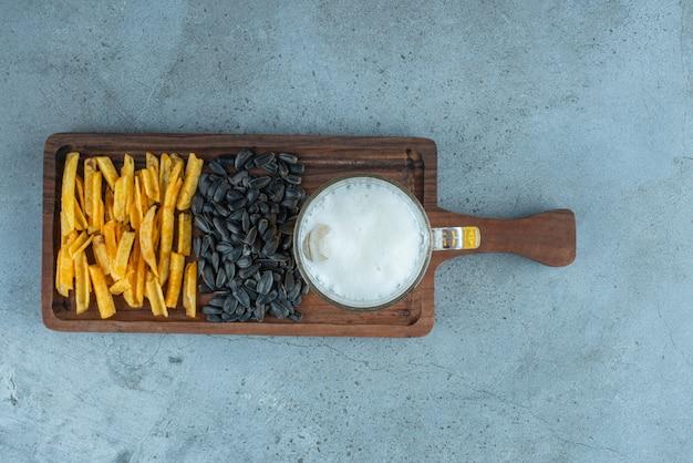 Frytki ziemniaczane, pestki słonecznika i szklanka piwa na desce, na niebieskim stole.