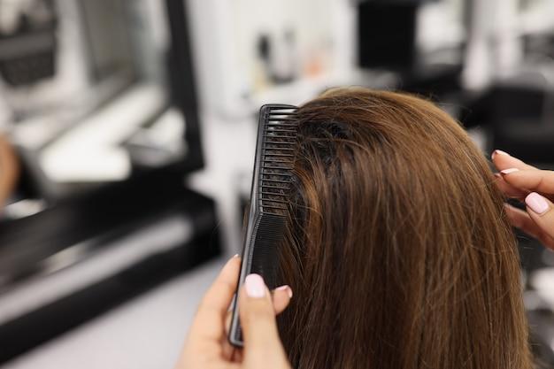 Fryzjer czesanie długich włosów klienta w salonie piękności zbliżenie. koncepcja usług fryzjerskich