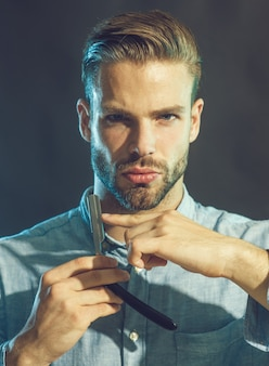 Fryzjer demonstrujący ostre ostrze akcesoriów fryzjerskich profesjonalny fryzjer z brodą i