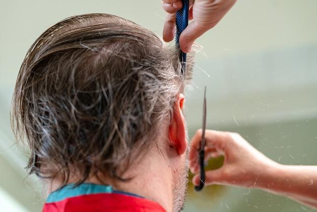 Fryzjer domowy strzyżenia włosów mans w pomieszczeniu. żona obcinająca mężowi włosy podczas kwarantanny.