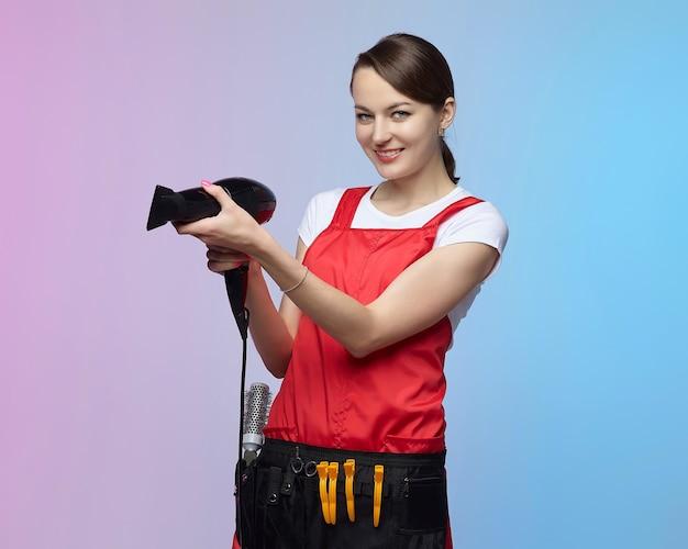 Fryzjer dziewczyna trzyma w rękach suszarkę do włosów. sesja zdjęciowa w studio