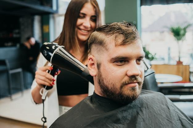 Fryzjer dziewczyna wysusza włosy do mężczyzny w salonie