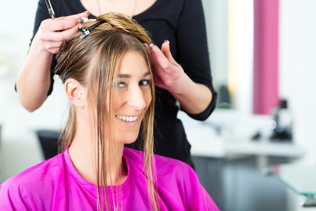 Fryzjer - fryzjerka strzyżąca włosy, klientka zostaje ostrzyżona