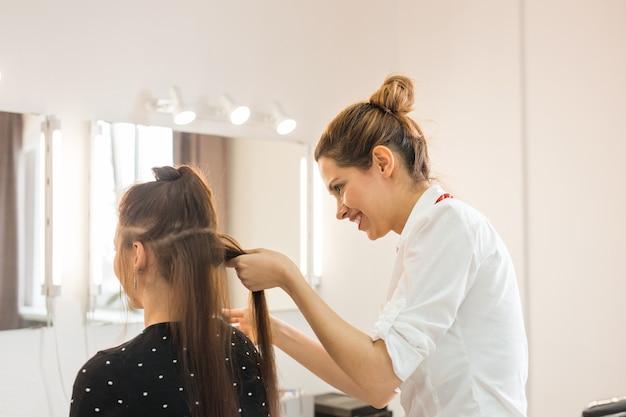 Fryzjer fryzura robi fryzurę dla młodej kobiety