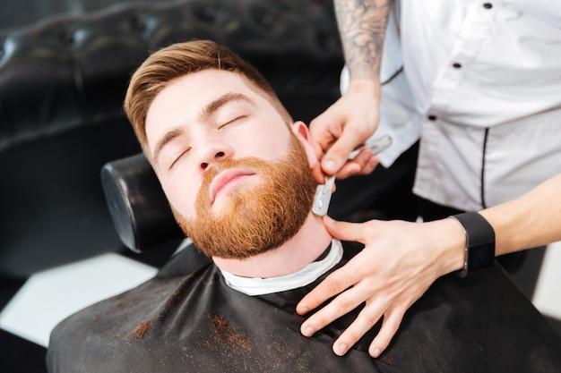 Fryzjer golący mężczyzna z brzytwą w zakładzie fryzjerskim