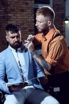 Fryzjer goli brodaty mężczyzna w sklepie fryzjerskim. brodacz odwiedzający fryzjera w salonie fryzjerskim.