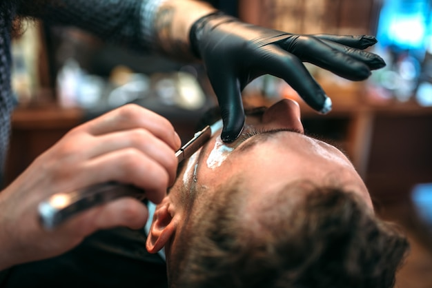 Fryzjer goli brodę brzytwą w zakładzie fryzjerskim.