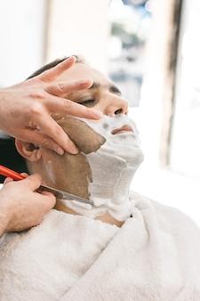 Fryzjer goli brodę człowiekowi z brzytwą w zakładzie fryzjerskim