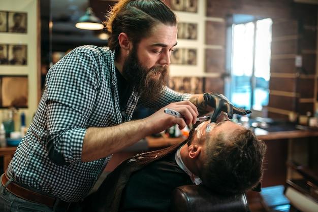 Fryzjer goli brodę klienta, goląc ostrzem w zakładzie fryzjerskim.