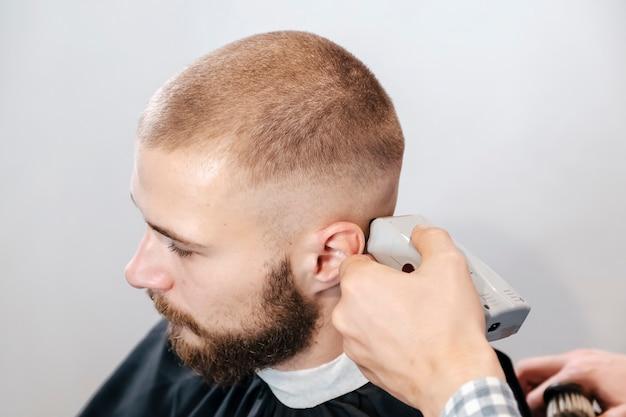 Fryzjer goli głowę brodatego klienta za pomocą trymera elektrycznego