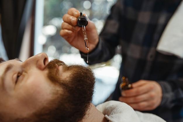 Fryzjer i klient, zbliżenie cięcia brody. profesjonalny fryzjer to modne zajęcie