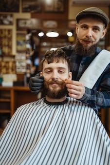 Fryzjer i klientka z wąsami, staromodne strzyżenie brody. profesjonalny fryzjer to modne zajęcie. męski fryzjer i klient w salonie fryzjerskim w stylu retro retro