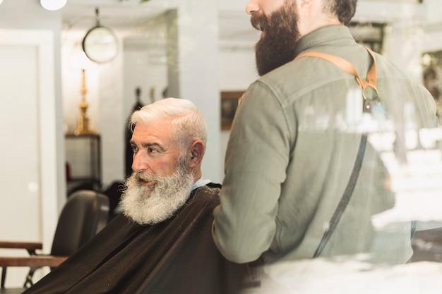 Fryzjer i starszy klient oceniający pracę