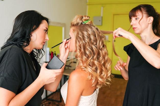 Fryzjer i wizażystka pracująca w salonie kosmetycznym z modelką