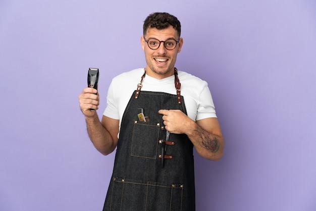Fryzjer kaukaski mężczyzna w fartuch na białym tle na fioletowo z zaskoczeniem wyraz twarzy