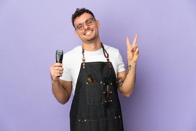 Fryzjer kaukaski mężczyzna w fartuch na białym tle na fioletowy uśmiechnięty i pokazujący znak zwycięstwa