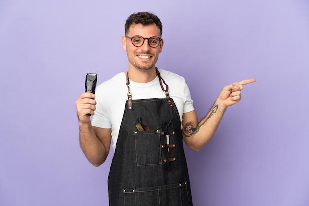 Fryzjer kaukaski mężczyzna w fartuch na białym tle na fioletowym palcem wskazującym z boku