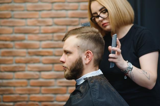 Fryzjer kobieta cięcia włosów mężczyzny w salonie fryzjerskim. kobieta pracująca jako fryzjer. koncepcja małej firmy.