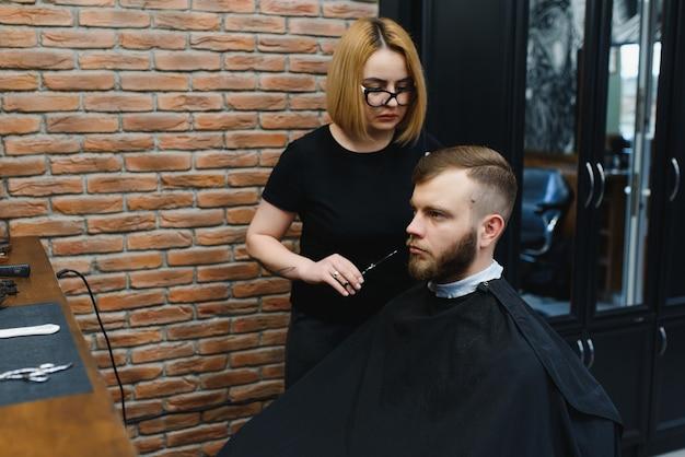 Fryzjer kobieta cięcia włosów mężczyzny w salonie fryzjerskim.