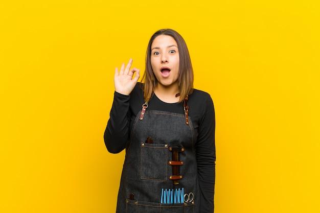 Fryzjer kobieta czuje się udana i zadowolona, uśmiechając się z szeroko otwartymi ustami, czyniąc znak ręką