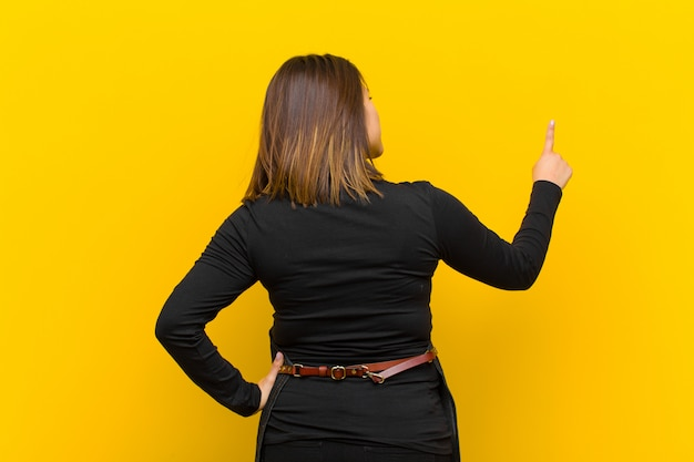 Fryzjer kobieta stoi i wskazuje protestować na copyspace, tylni widoku pomarańcze